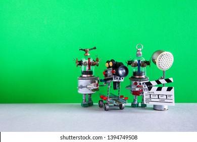 El asistente de foco de claqueta de cámara robot divertido graba comedia dramática con elementos de una película de terror, película de acción y aventuras. Película robótica detrás del escenario. Fondo verde