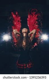Delicate beautiful brunette woman posing with  red dark angel wings. Studio shot.
