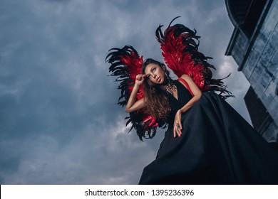 悪魔、悪魔、夜空の背景として服を着た女性sexi。翼を持った女の子のセクシーな悪魔、欲望に満ちた悪魔。セクシーな悪魔の概念。情熱的な顔の女性は役割ゲームをします。悪魔のセクシーな女の子は髪で遊ぶ。