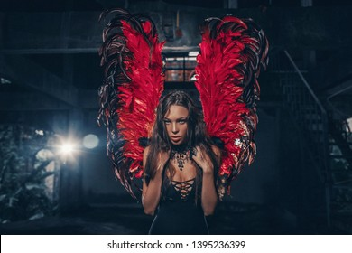 Art photo of an Dark Angel beautiful woman. A girl with red devil wings and a black dress in the dark room