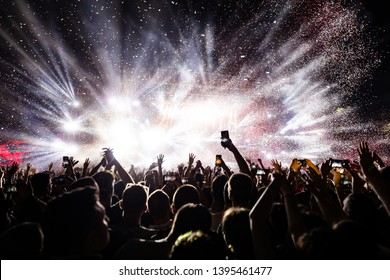 Excited audience watching confetti fireworks and having fun on music festival at night. Copy space.