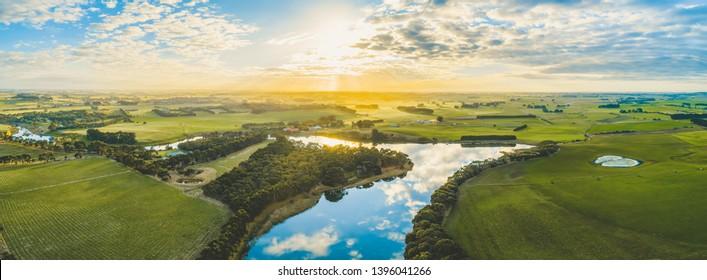 風光明媚なオーストラリアの田園地帯の草原と牧草地に沈む夕日と川が流れる-空中パノラマ