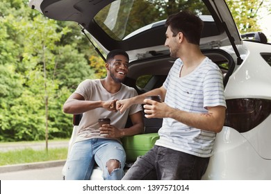 Young multicultural male friends sitting in open car back, drinking coffee with brofist gesture
