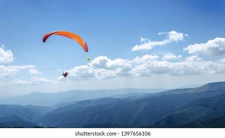青い空のパラグライダー。パラグライダーで飛んでいるスポーツマン。