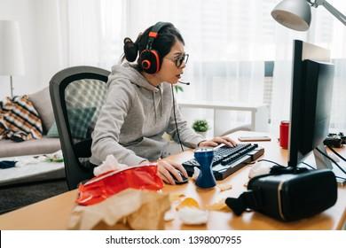テクノロジーゲームエンターテインメントの人々の概念。PCコンピュータでヘッドセットの若いアジアの高校生の女の子は家でゲームをしながらジャンクフードのおやつを食べます。ストリーミングプレイスルーウォークスルービデオ