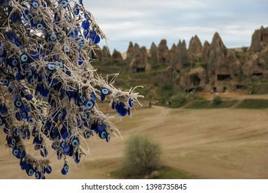 Una vista cappaddociana de la antigua ciudad de la cueva con nazars, amuletos que protegen de un mal de ojo colgado de una rama arriba