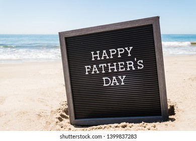 Happy Father's day background with black board on the sandy beach near the ocean.