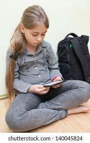 床に座って電子書籍を読む10歳の少女