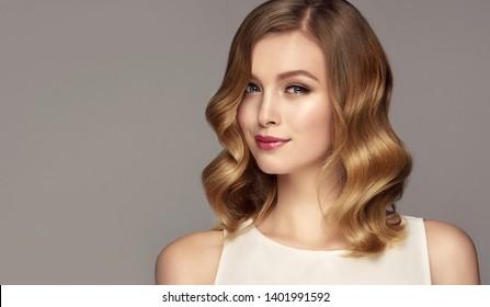 Blondevrouw met mooi krullend haar op grijze achtergrond. Het meisje met een prettige glimlach. Kort kapsel . Bob kapsel