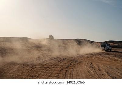 Wettkampfrennen Herausforderung Wüste. Auto überwindet Sanddünen Hindernisse. Auto fährt mit Staubwolken im Gelände. Hindernisse für Offroad-Rennen in der Wildnis. Endlose Wildnis. Rennen in der Sandwüste.