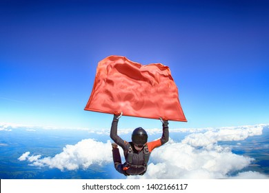 Banner sky diving. Falling people take red flag. Black suit and white clouds