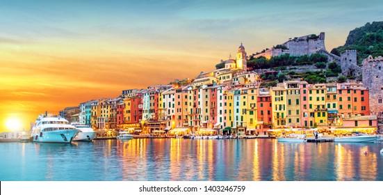 Mystische Landschaft des Hafens mit bunten Häusern und den Booten in Porto Venero, Italien, Ligurien am Abend im Licht der Laterne bei Sonnenuntergang