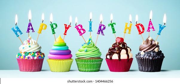 Cupcakes coloridos con velas deletreando feliz cumpleaños