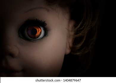 Close-up scary vintage doll face isolated on black background. Soft backlight, focus on eye. Halloween concept