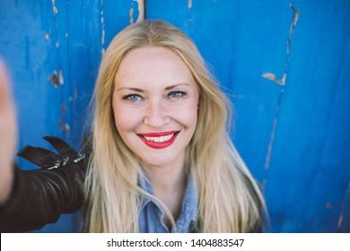 Retrato de mujer rubia sonriente con ojos azules (haciendo selfie) sobre fondo vintage