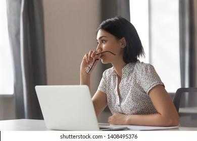 思いやりのある不安なアジアのビジネスウーマンは、職場で問題を解決することを考えて目をそらし、心配している深刻な若い中国人女性は、ラップトップで座っていることを反映して考えに迷いました
