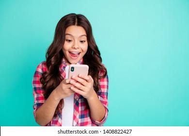 Portret van haar ze mooi aantrekkelijk mooi charmant schattig vrolijk vrolijk golvend pre-tienermeisje in geruit overhemd online browsen geïsoleerd over heldere levendige glans groen blauwe turkooizen achtergrond