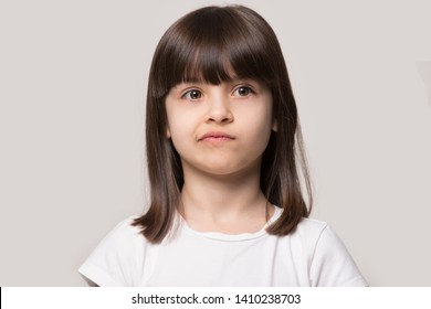 Upset brown-haired fringe hairstyle small girl pucker up her mouth feel upset or dissatisfied head shot studio portrait on beige background, concept of naughty kid, anxieties of little person concept