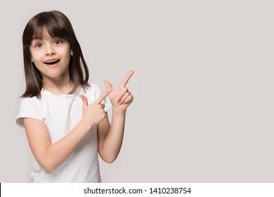 灰色のベージュ色の背景に分離された6歳の茶色の髪の少女、ヨーロッパの外観の子供は、広告テキストの概念のコピースペースの空き領域でカメラ人差し指を脇に見て不思議に思う