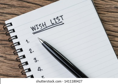 Wish list concept, pen on white paper note pad with handwritten headline as Wish List and numbers listed on wood table in soft tone, things wanted or next time purchase.