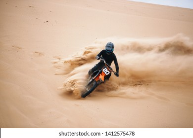 Motociclista en una motocicleta de cross-country ir rápido en el desierto con salpicaduras de arena