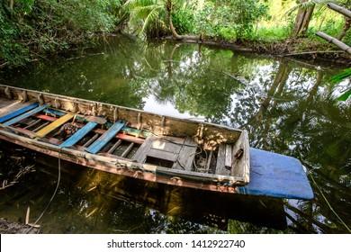川沿いに停泊する漁船を背景に、風が吹く自然(木々、竹林)に囲まれた雰囲気。