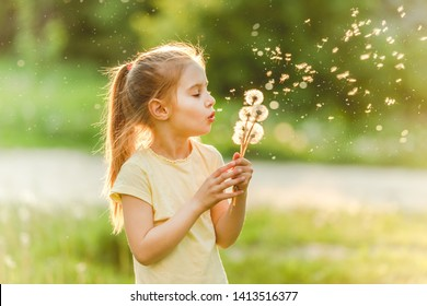 Beatiful girl child loves to spend her leisure at meadow, collecting flowers and playing with dandelions