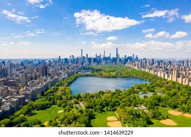 Luftaufnahme des Central Park in New York mit Golffeldern und hohen Wolkenkratzern, die den Park umgeben.