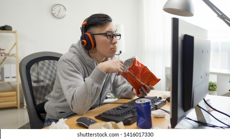 funny asian man with headphones plays video games on computer and eats snack from pack. japanese otaku gamer in glasses enjoy chips while watching anime cartoon movie on pc screen on summer break.