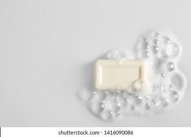 Barra de jabón y espuma sobre fondo blanco, vista superior. Maqueta para diseño