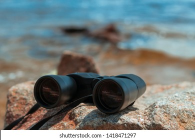 Binoculars on the stone. Black military binoculars lying on a red stone against the backdrop of the bay