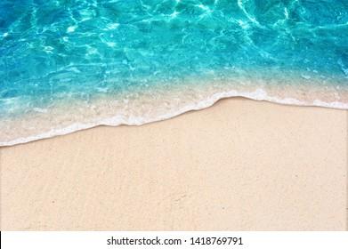 Weiche blaue Ozeanwelle auf sauberem Sandstrand