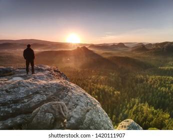 Mann auf dem Felsenimperium mit Händen in der Hosentasche wacht über das neblige Morgental bis zur aufgehenden Sonne am Horizont.