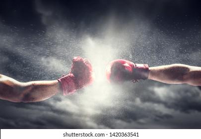 Twee bokshandschoenen slaan. Licht op bewolkte hemel. Doos, kracht, vechtsymbolen.