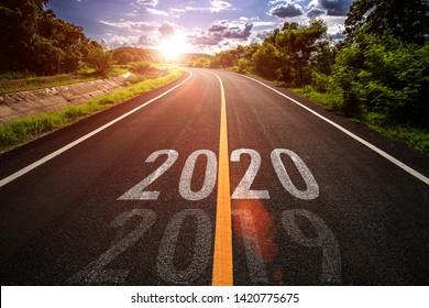 黄金の夕日と美しい青い空の空のアスファルト道路の真ん中にある高速道路に書かれた2020年の言葉。2020年の新年のコンセプト。