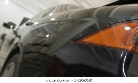 Rückansicht eines schwarzen Neuwagens im Autohaus, Luxuskonzept. Kunst. Nahaufnahme für rotes Rücklicht und polierte Fahrzeugflügel, Karosseriedetails.