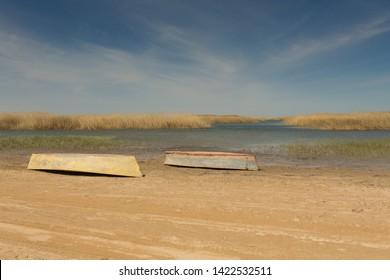 Ein Boot wurde auf den Kopf gestellt. Ruderboote im Schilf. Holzboot an einem grasbewachsenen Seeufer an einem Sommertag. Aralsee, Kasachstan