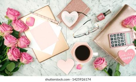 Ultra femininer rosa Schreibtischarbeitsplatz mit roségoldenen Accessoires auf weißem Marmorhintergrund Flatlay Overhead.