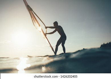 Silhouette of surfer balancing on windsurf board. Low angle splashing view of windsurfer. Windsurfing, sailing, water sports, extreme