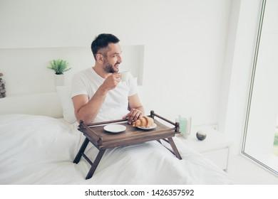 Foto de cerca, increíble, él, su macho, mirada, ventana, mañana, dulce, azucarado, panadería, desayuno, café, bebida, té, mesa, edredón, blanco, dormir, camiseta, acostado, cama, habitación luminosa, casa, interior