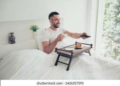 Cerrar foto increíble él él su chico buenos días concepto dulce panadería desayuno café pequeña mesa de té cambio de canal mostrar ropa de dormir blanca ropa de dormir camiseta acostado cama habitación luminosa casa interior
