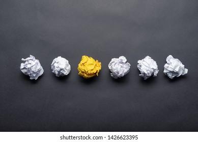 Bola de papel amarillo arrugado entre bolas blancas sobre fondo negro. Extraordinaria solución de problema. Motivación empresarial con espacio de copia. Experiencia única y diferente. Generación de ideas