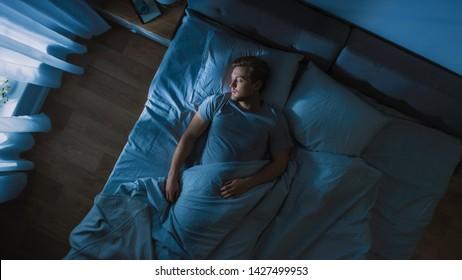 夜に彼の寝室のベッドで居心地の良い眠っているハンサムな若い男の上面図。窓越しに輝く冷たい弱い街灯のある青い夜の色。