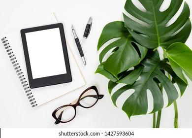 Flache lag tropische Dschungel Monstera Blätter, Papier Notizbuch, E-Book-Reader, Brille auf weißem Hintergrund. Draufsicht weibliches Tagebuch, Briefpapier und elektronisches Gerät auf Home-Office-Schreibtisch.