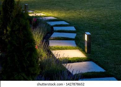 marmeren pad van vierkante tegels verlicht door een lantaarn die gloeit met een warm licht in een achtertuin met een bloembed en een gazon kopie ruimte.