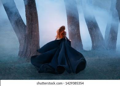 schwarze Witwe langes dunkles Seidenfliegen-Stoffkleid, gruselige Horrorfrau rotes Haar läuft mysteriöser Wald abgewandt schwarze Dame Nachtspaziergang gotischer blauer Nebel Naturbaum. Kunst Fotoshooting mysteriöse Frau Silhouette