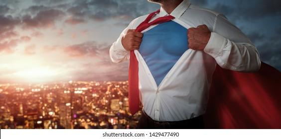 Junger Geschäftsmann, der sich wie ein Superheld verhält und sein Hemd über der Stadt bei Sonnenuntergang mit Kopierraum abreißt