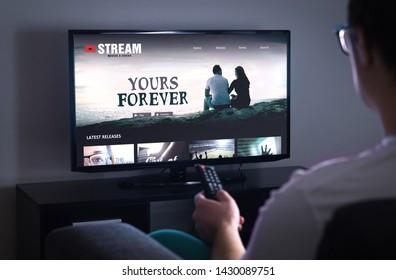 スマートテレビのオンライン映画ストリームサービス。テレビのオンデマンドビデオ(VOD)サービスを備えたストリーミングシリーズ。リモコンで見る映画を選ぶ男。夜遅くに自宅のソファに座っている人。