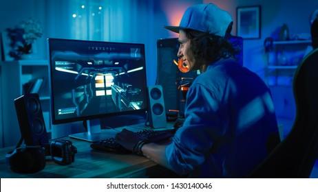 Professionele gamer speelt first-person shooter online videogame op zijn krachtige personal computer met kleurrijke neon led-verlichting. Jonge man draagt een pet. Woonkamer verlicht in rustige stijl. Avond