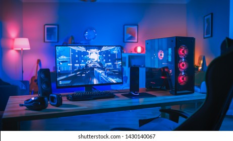 Powerful Personal Computer Gamer Rig with First-Person Shooter Game on Screen. Monitor Stands on the Table at Home. Cozy Room with Modern Design is Lit with Pink Neon Light.